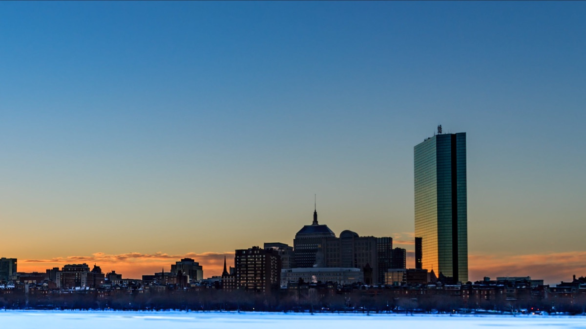Part of Boston's skyline along a frozen Charles River with a low orange and blue glow from the rising sun.