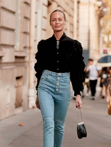 Stylish woman in black bubble sleeve top and high-rise jeans