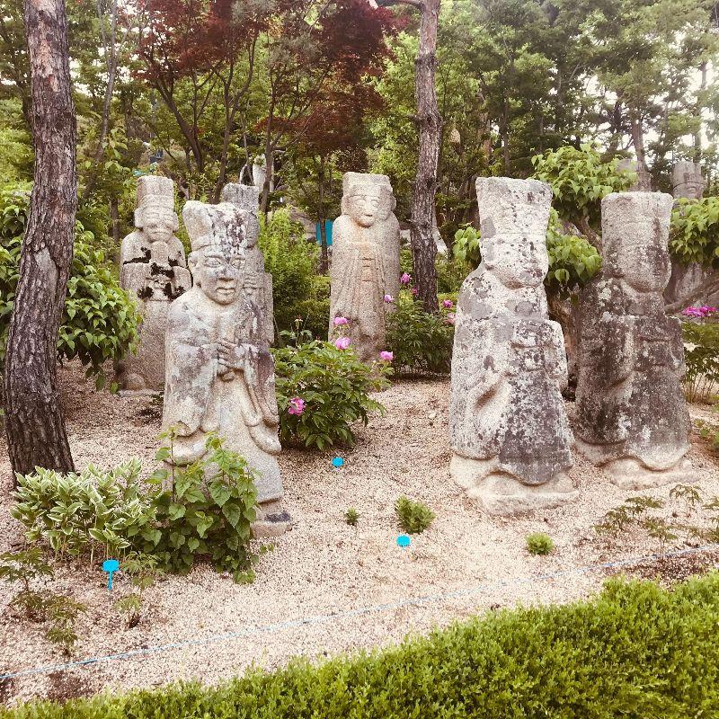 Korean stone sculptures from the Joseon Dynasty, in an outdoor exhibit at the Korean Stone Art Museum. Eight light stone sculptures, in the form of human figures with hands clasped, stand in a grove of gravel, bushes, and trees