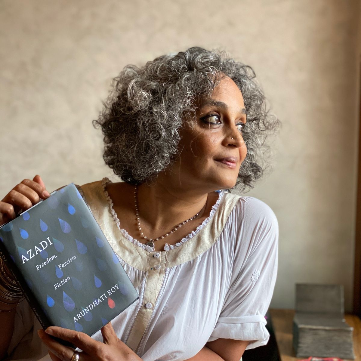 Arundhati Roy holds a copy of her new book Azadi