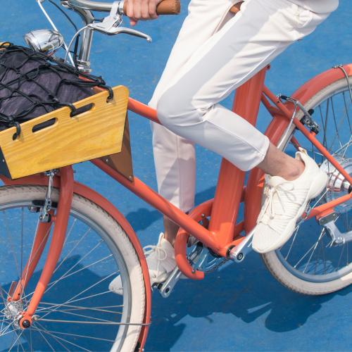 Mulher andando de bicicleta em quadra azul