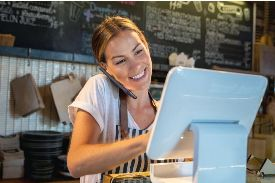 woman behind cafe counter on the phone