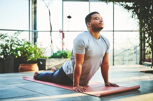Male in yoga cobra pose on a yoga mat | vinyasa yoga | pura vida physio | clare kelly