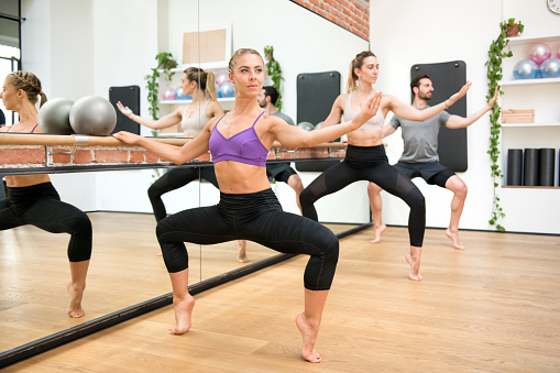 Blonde female standing at ballet barre in second position plie | pilates barre class | pura vida physio | clare kelly