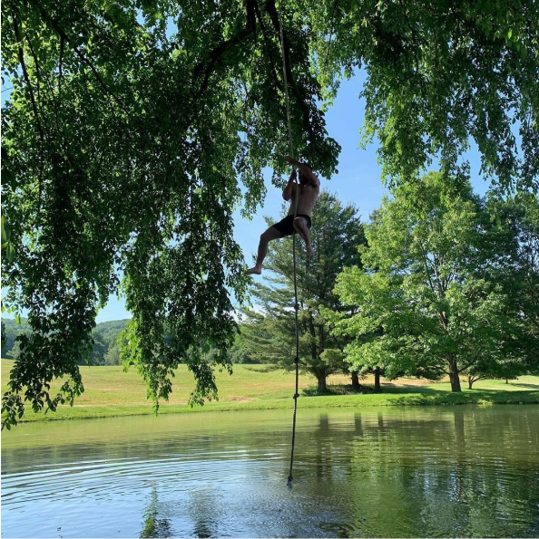 Person climbing rope above lake