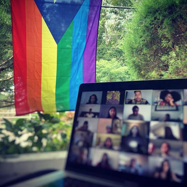 Zoom video on laptop with rainbow flag in the background