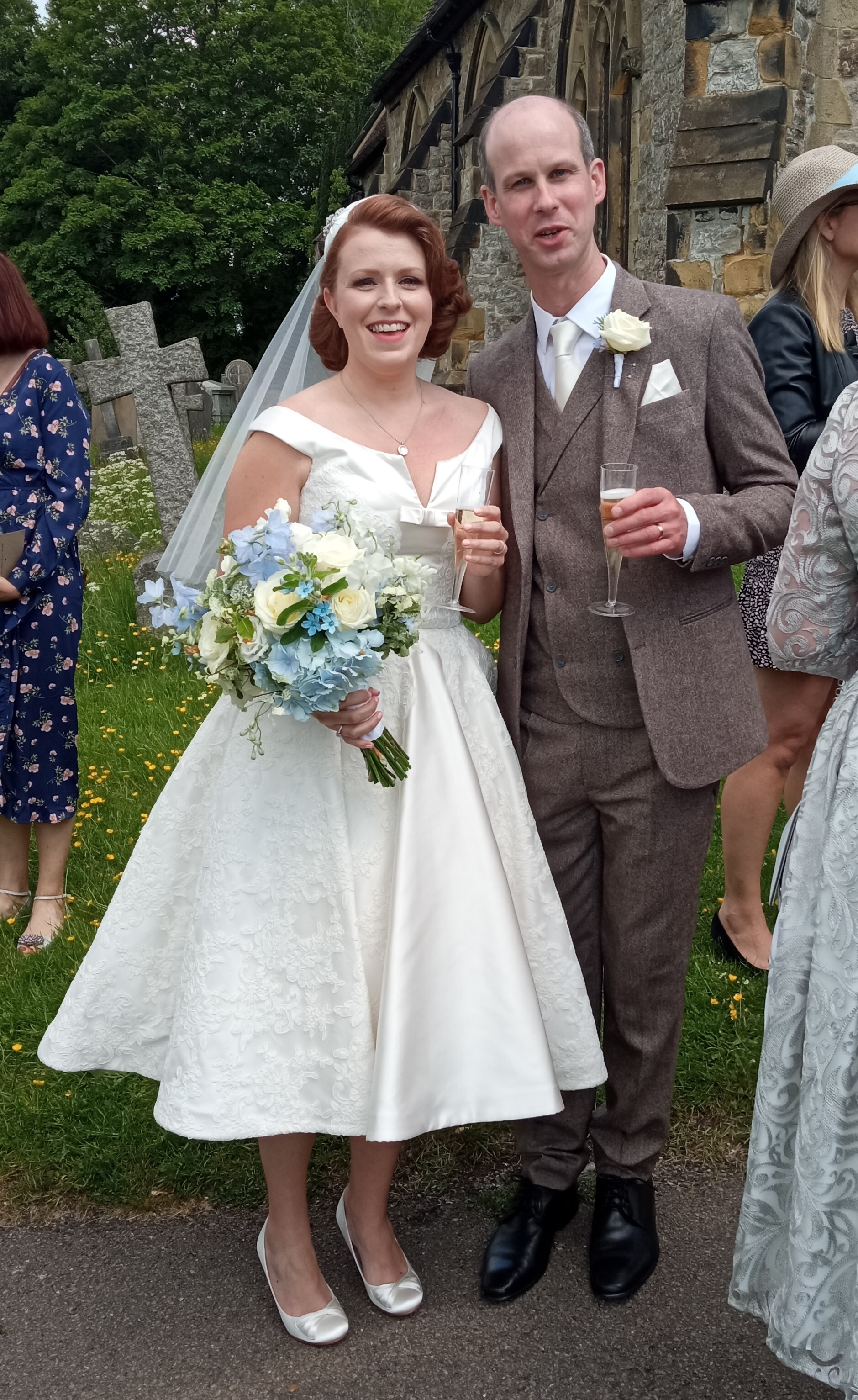 Abbey and Tom enjoy a glass of bubbly outside the church after their wedding