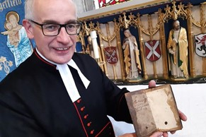 Rev Canon Keith Farrow with the 300 year old book The Faith and Practice of a Church of England Man