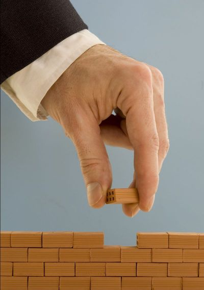 Photo of a hand building a wall with tiny bricks