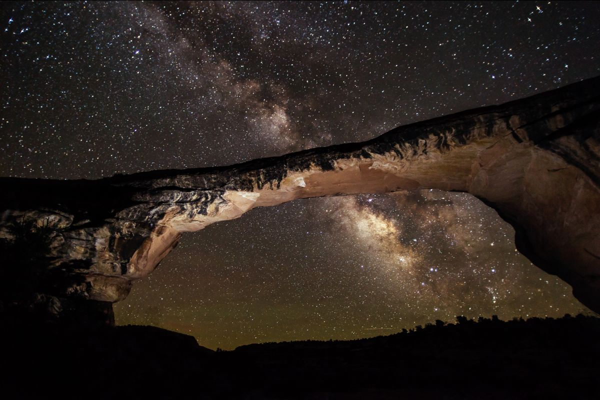 The brilliant white cloud of the Milky Way visible among a starry sky behind Natural Bridges National Monument's massive stone bridge called Owachomo.