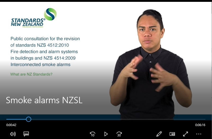 Video still showing a man signing and reading: Smoke Alarms NZSL. Public consultation for the revision of standards NZS 4512:2010 Fire detection and alarm systems in buildings and NZS 4514:2009 Interconnected smoke alarms