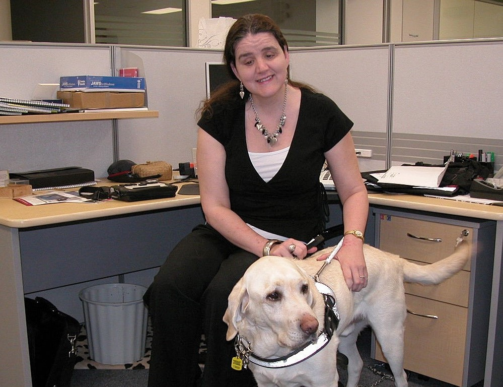 Martine sits at an office desk with her guide dog