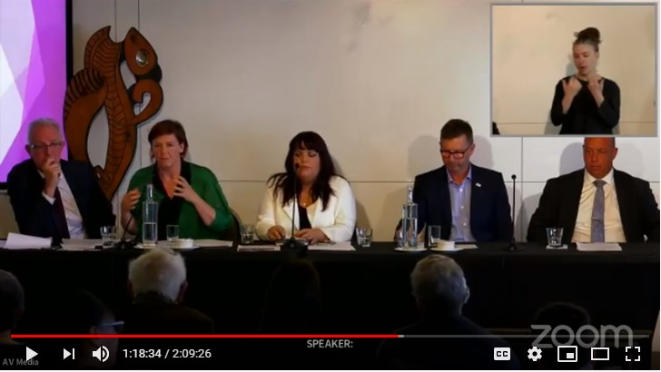 A video still from the election event shows the five candidates seated at a long table with microphones and a sign language interpreter in a window in the corner of the screen