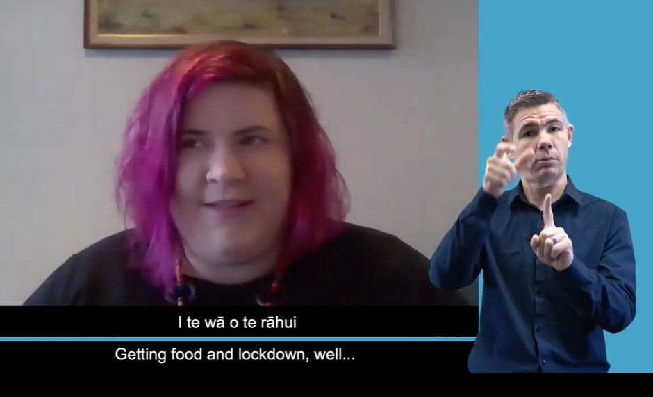 """A video still shows Prudence to the left with a sign language interpreter to her right and captions below. The top line reads """"I te wā o te rāhui"""". The line below reads """"Getting food in lockdown, well"""""""