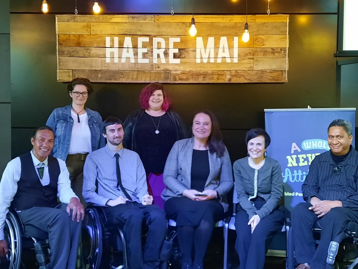 Posing for the photo under a sign that reads 'Haere Mai' are the Mahi Tika- Equity in Employment team Rodney Bell, Tim Young, Angela Desmarais and Prudence Walker with Minister for Disability Issues Carmel Sepuloni, Disability Rights Commissioner Paula Tesoriero and Ike Rākena, Mana Whenua, Enabling Good Lives
