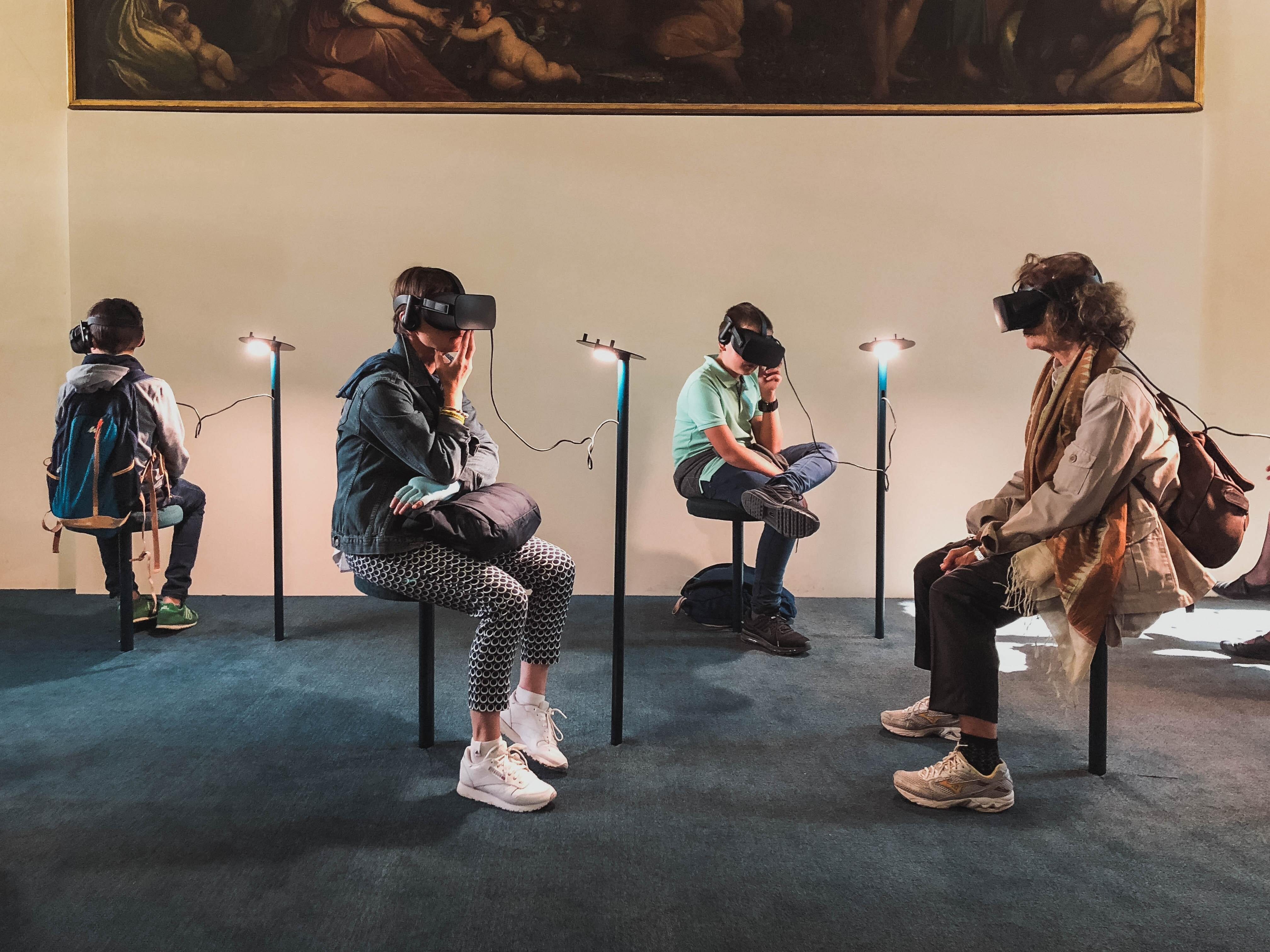 four people sit on stools wearing VR headsets