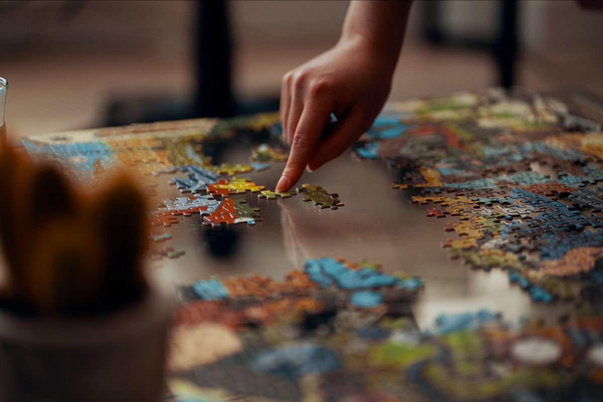 Jigsaw puzzle with hand moving a piece