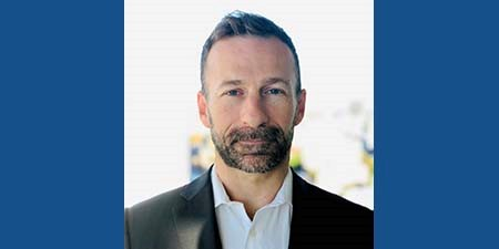 This is a photo of Paul Miller, the New South Wales Ombudsman. He has fair skin, blue eyes, short hair, and a beard. He is wearing a dress shirt and blazer.