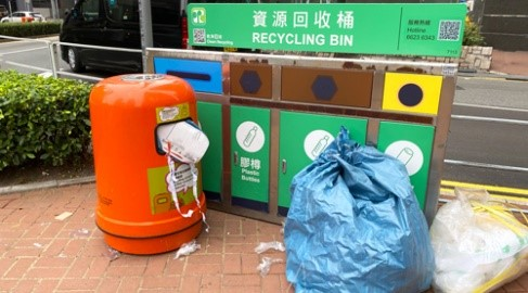 A municipal recycling bin on a city street has four separate containers for different types of recyclable materials. The containers are blocked by an overflowing trash can and two full rubbish bags.