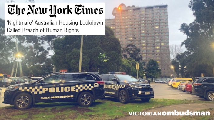 This is a photo of a high-rise apartment building with a parking lot in the foreground. Two police vehicles are parked on a grassy area of the parking lot. A headline from The New York Times overlays the photo. The headline reads: 'Nightmare' Australian Housing Lockdown Called Breach of Human Rights. The Victorian Ombudsman logo is placed at the bottom right corner of the photo.
