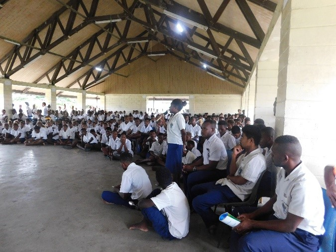 A large crowd of Selwyn College students sit together inside a building. One student is standing with a microphone in hand. They are asking a question about corruption to Mr Nelson Dhita, Director Legal Services Unit of the Ombudsman Advocacy team, during his presentation on the roles and functions of the Ombudsman.