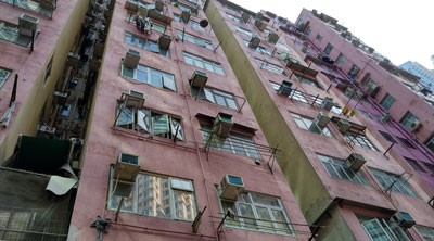 A mid-rise apartment building has been photographed from an upward angle. Most of the windows have air conditioning units jutting out of them. There are poles installed beneath many of the windowsills, which tenants use as laundry lines.