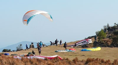 Many people are standing in an open field under a clear sky. Pieces of paragliding equipment are lying on the grass. One person is holding a glider aloft in the air.