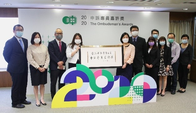 Eleven people in business attire and facemasks stand side-by-side in front of a backdrop. The backdrop features both Chinese and English text. The English text reads: The Ombudsman's Awards 2020. Two women in the centre of the group hold up a commemorative sign written in Chinese. A large floor sign stands in front of the group. The floor sign spells out '2020' in abstract shapes.