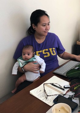 Jul and her baby sit at a desk.