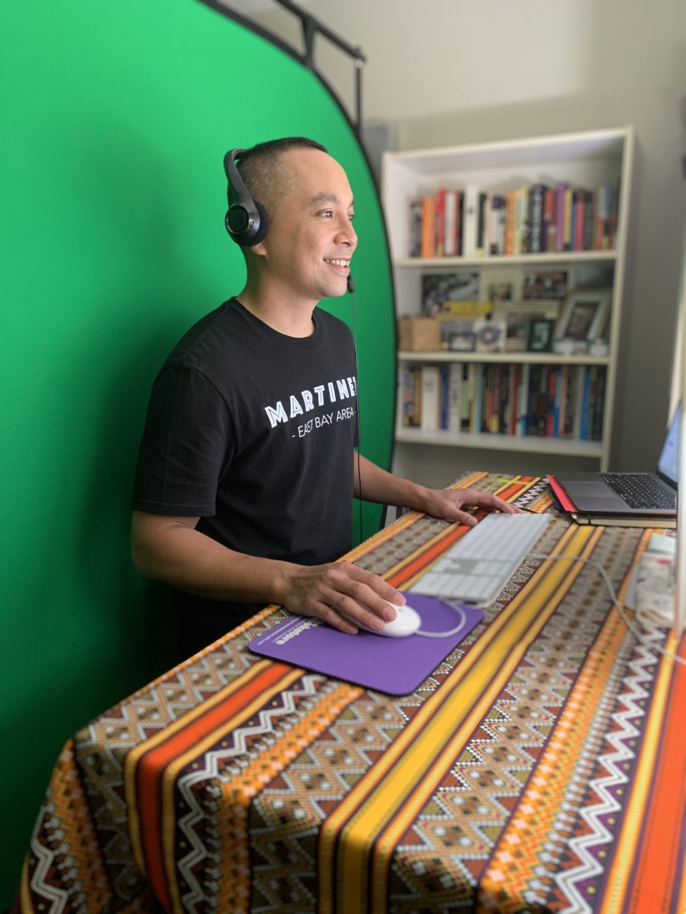 Mark Bautista stands at a desk in front of a green screen.