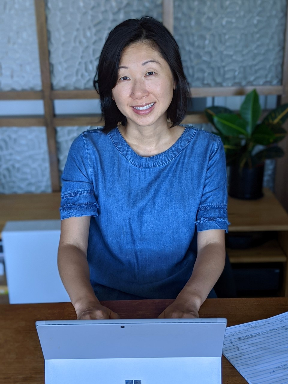 Agnes Hong sits at a desk, posing for a photo