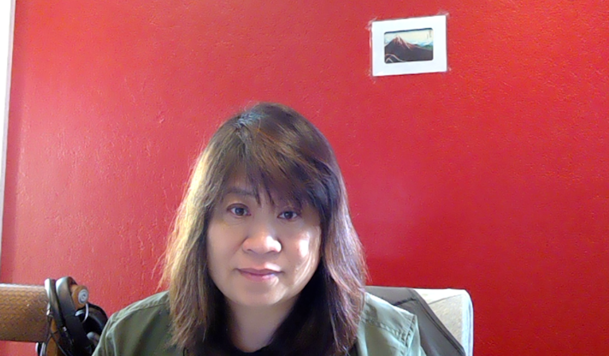 Fang-yu Chou sits in front of a red wall