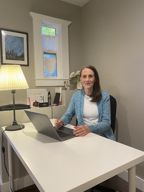 Casey Nesbit sitting at a desk in her home office.