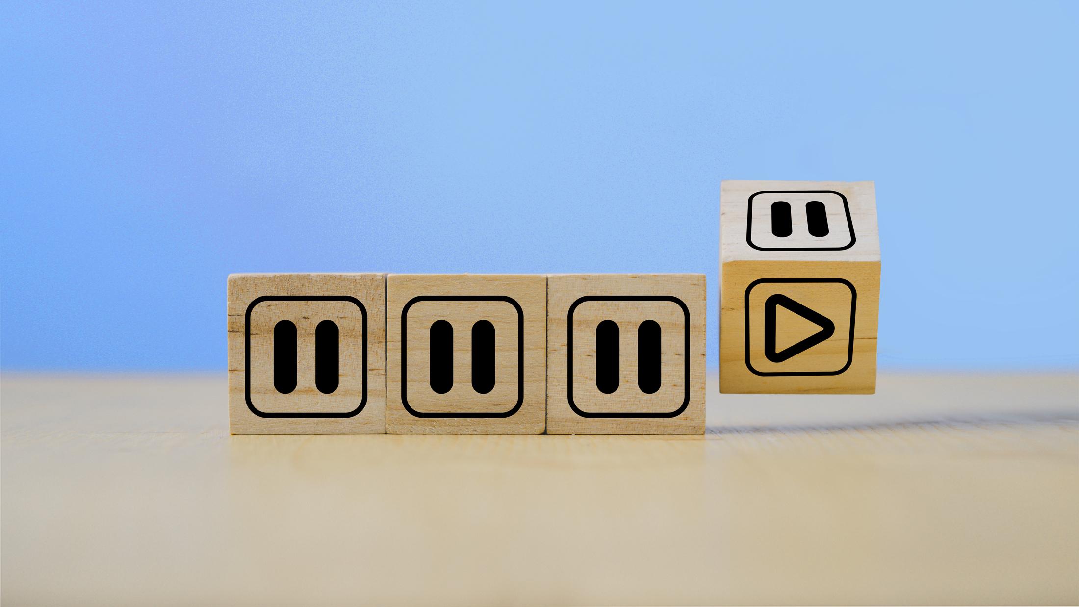 Four wood blocks displaying a pause symbol.