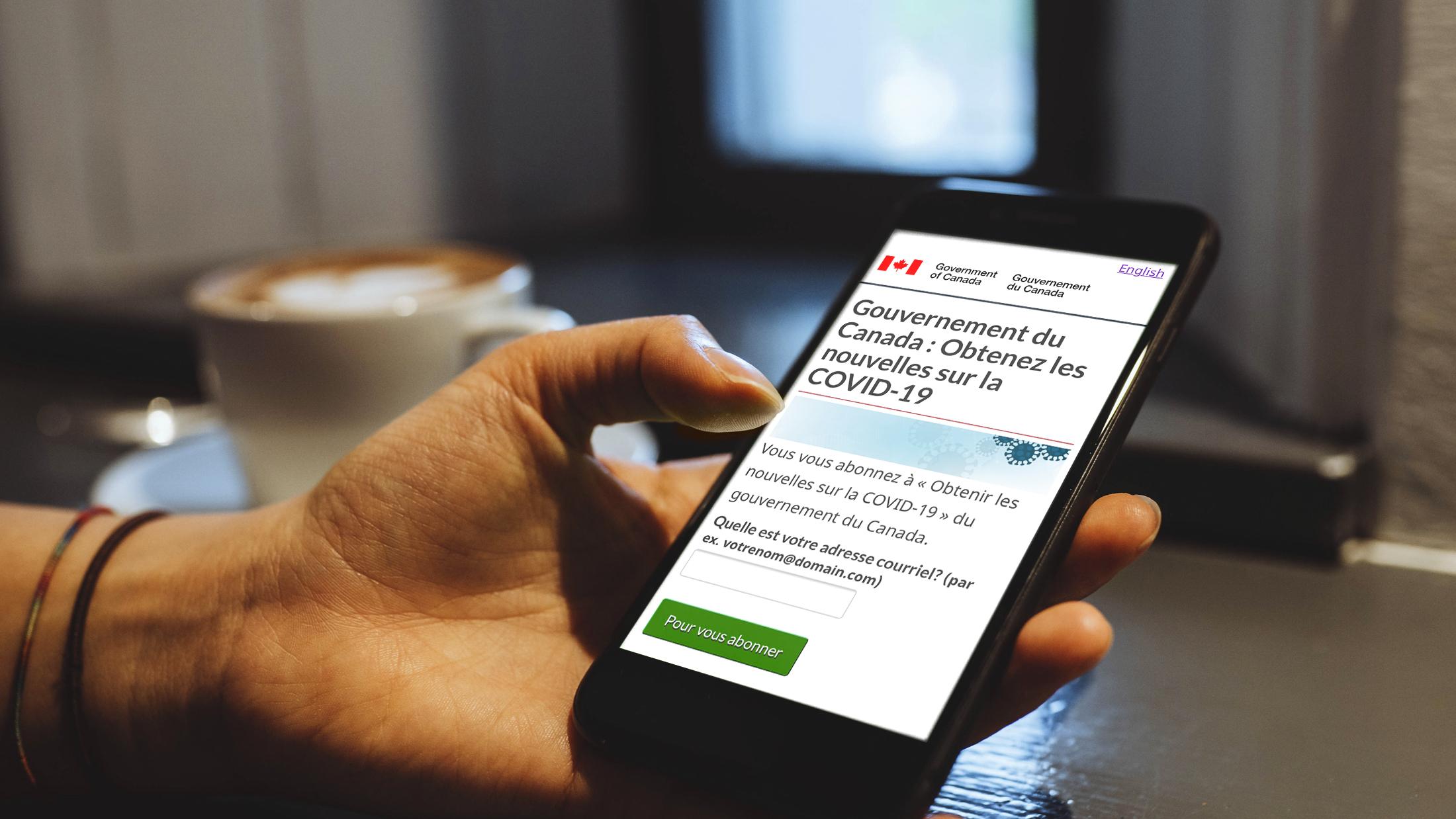 Un téléphone affichant « Gouvernement du Canada : Obtenez les nouvelles sur la COVID-19 », un service d'abonnement par courriel qui envoie aux Canadiens et Canadiennes d'importantes mises à jour sur la COVID-19.