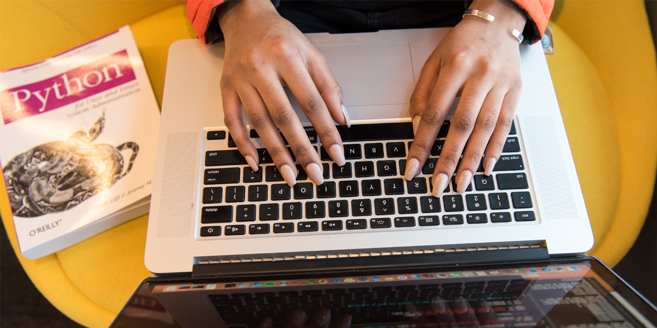 Close up photo of a woman hands typing on a laptop keyboard next to a book.