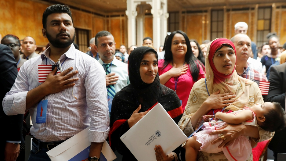 Group of people with hands over chest during Citizenship Naturalization Ceremony