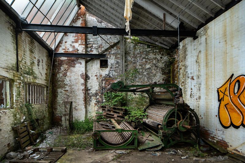 Derelict factory room with glass roof and disused machinery on the floor