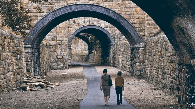 Two people walking along a path on a disused railway line underneath a series of arches