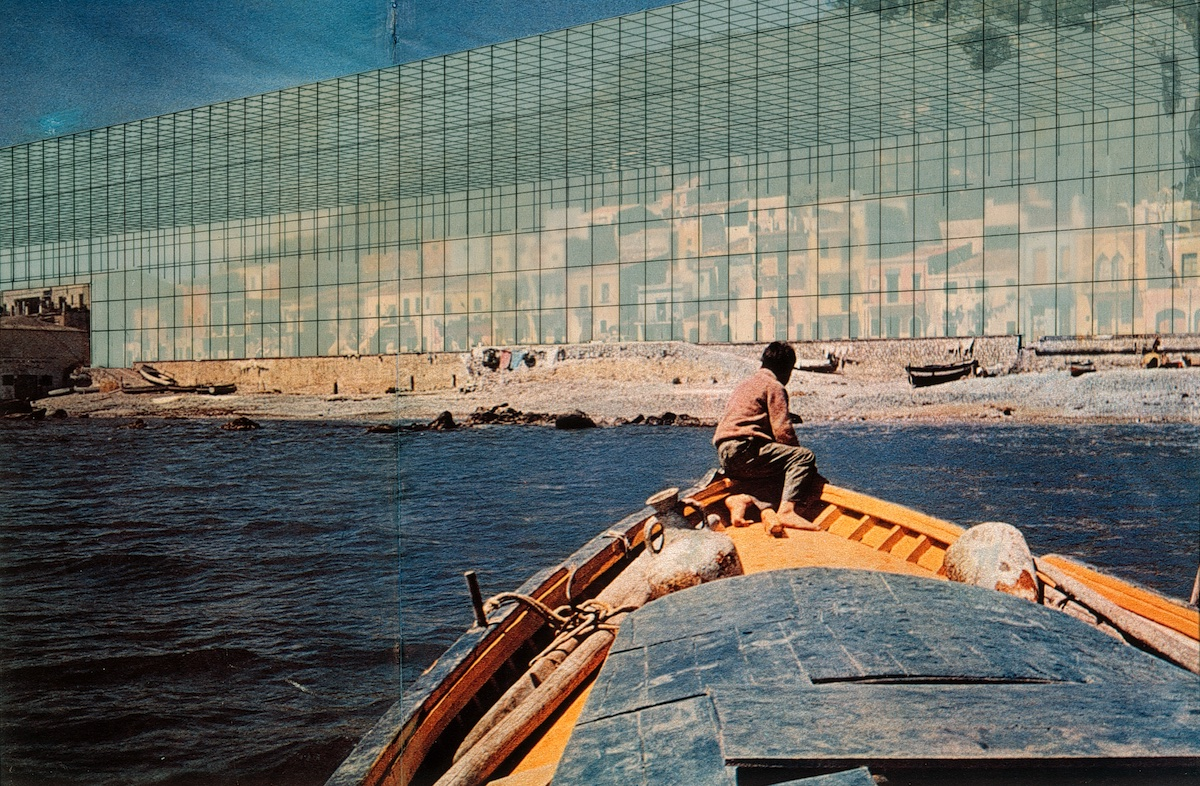 A photograph of a person sitting at the prow of a small boat, facing away from the camera, facing a shore fronted by a huge semi-translucent geometrical wall that seems to enclose a city.