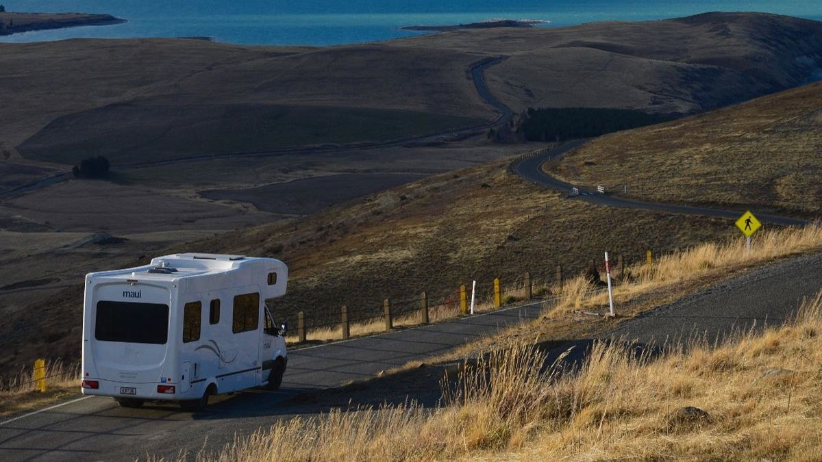 RV driving down winding empty road with tall, yellow grass on either side.
