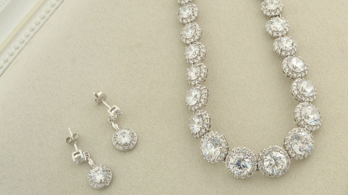Diamond earrings and necklace on white leather pad.