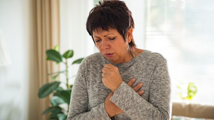 A mature woman coughing and holding her chest.