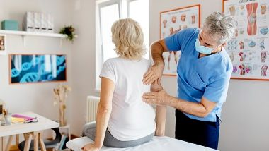 Senior woman having her back examined in GP surgery