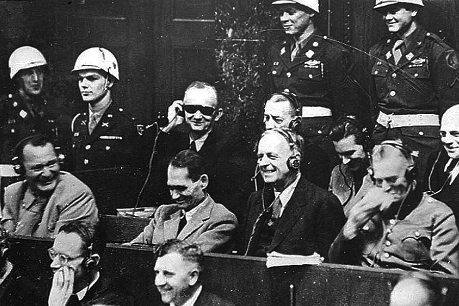 The defendants (and even some of the guards) sharing an unplanned moment of laughter during the otherwise very serious proceedings.(Photo: unknown photographer)