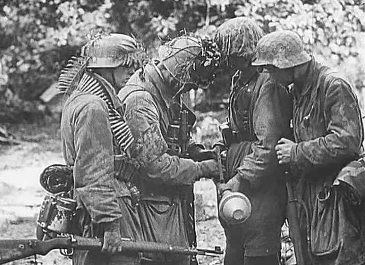 A group of German paratroopers using different kinds of camouflage on their helmets (net, cover, foliage with a strap) in Normandy(Photo: Bundesarchiv)