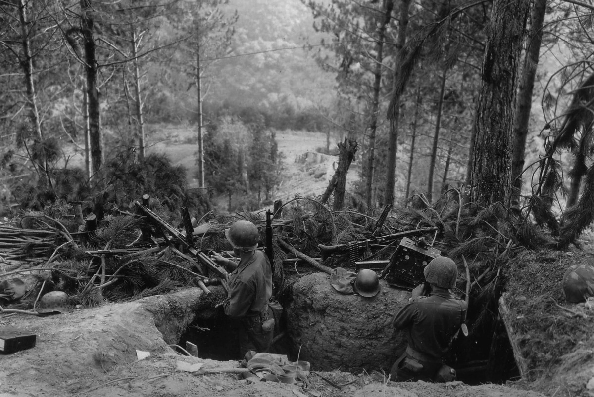 American soldiers examine a captured German machine gun position in the forest (Photo: U.S. Army)