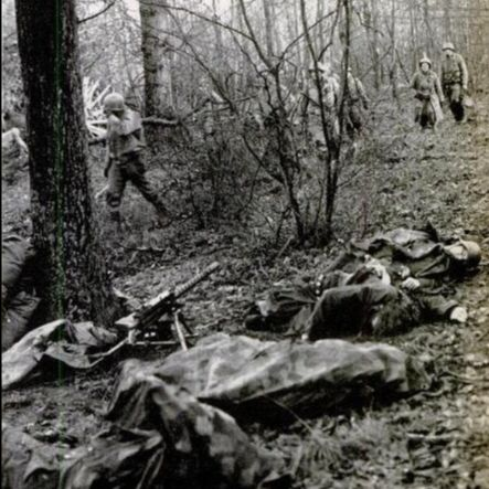 American soldiers marching past a group of dead Germans who were all killed by a single grenade. The Germans were equipped with a captured American .30 caliber Browning machine gun. (Photo: U.S. Army)