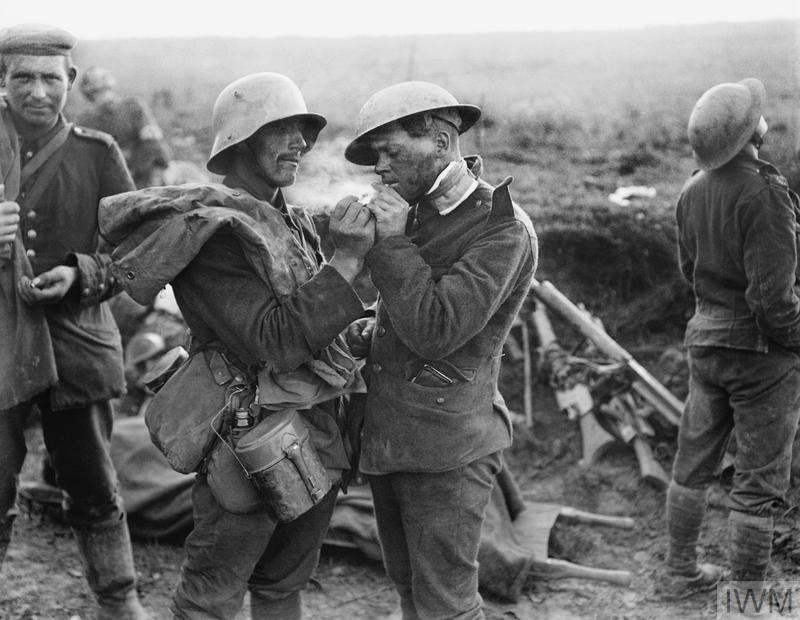 A German soldier in a Stahlhelm and a British soldier in a Brodie helmet sharing a cigarette in 1918(Photo: IWM)