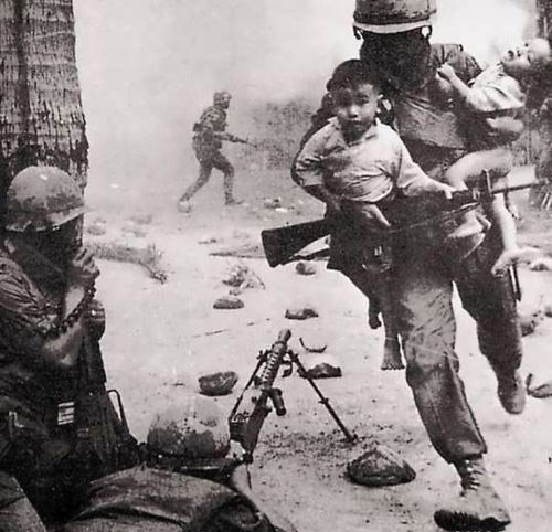 An American infantryman covering his squad members with an M1919A6 while the others move Vietnamese children out of the line of fire(Photo: historicalfirearms.info)